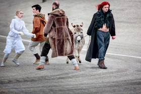 An old man and a young man, a person dressed in white and a man dressed in dark colours with long red hair and a donkey, all moving on tarmac