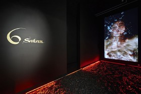 "A black room with the writing ""6 Satan"" and a video projection on the wall"