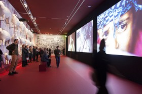 Visitors in a red room, on the left sculpures of white sheep, on the right video projection