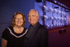 Portrait of a couple in an exhibition room, in the background sculptures of white sheep