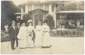 Black and white photo of two men and three women in a park in front of a house