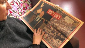 A woman is reading a hebrew newspaper with pictures of Rabin and the peace rally.
