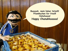 "A puppet in a blue shirt with the star of David, in front of a crate of Berliner hotcakes with a speech bubble, ""Oooh, my oh my! Hotcakes for free!!! Hahahaaaa! Happy Hanukkaaaah!"""
