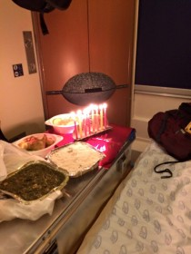 In a sleeping car on the train, a metal suitcase covered by a meal on plastic and aluminum plates, next to it a candelabrum with eight lit candles.