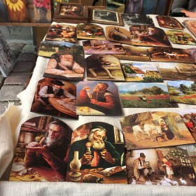 "A table with paintings of ""lucky jews"", animals, flowers, and farm scenery"