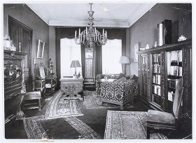 Black and white photography of a study, decorated with antiques and paintings