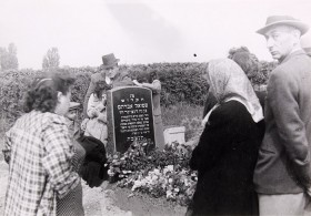 Black and white photograph of people at a grave