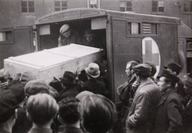 Black and white photograph of a coffin transported into a car