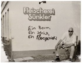 "A man with a beer bottle sitting in front of a wall with the instription ""Butcher's shop Sünkler"""