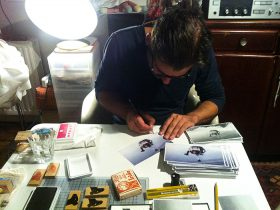 Benjamin Seide signing the cards in Birgits apartment