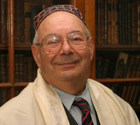 Portrait of an elderly man with glasses, kippah and tallit.