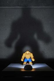 Action figure with huge shadow behind it on the wall