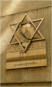 Commemorative plaque in form of a Magen David containing a broken relief of the synagogue