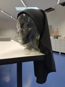 Transparent bust wearing a black veil.