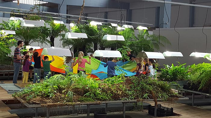 Children stand between rows of plants in the Diaspora Garden, in a circle around a colorful cloth.