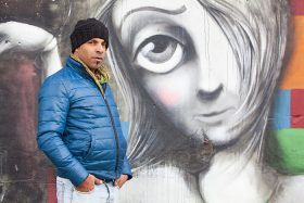 A man with woolen hat and warm jacket in front of a graffiti