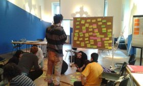 Several people are sitting or standing in a room, working with colorful notes; some notes have already been attached to a pinboard