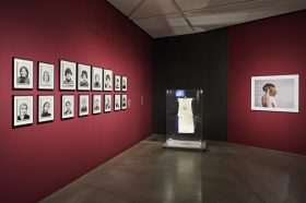 View of a room in the exhibition with portraits of women on one wall, a dress in a glass case, and a photo of a woman with two wigs on another wall.