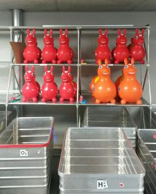 Red rubber bouncy animals that resemble horses on a gray shelf behind empty wheeled containers