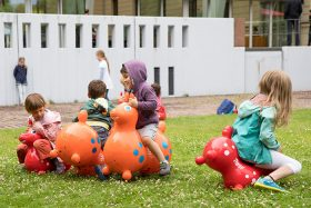 In the museum garden, four children ride the rubber animal mentioned in the text
