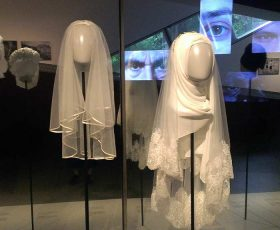 two white head coverings for women displayed in the exhibition