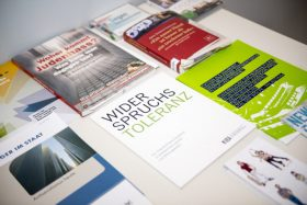 "Various brochures lie on a table, with titles such as ""Where does hatred of Jews come from?"""