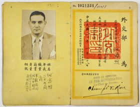 Yellow pages of a passport with Chinese letters, opened on the page with the photograph and a red stamp