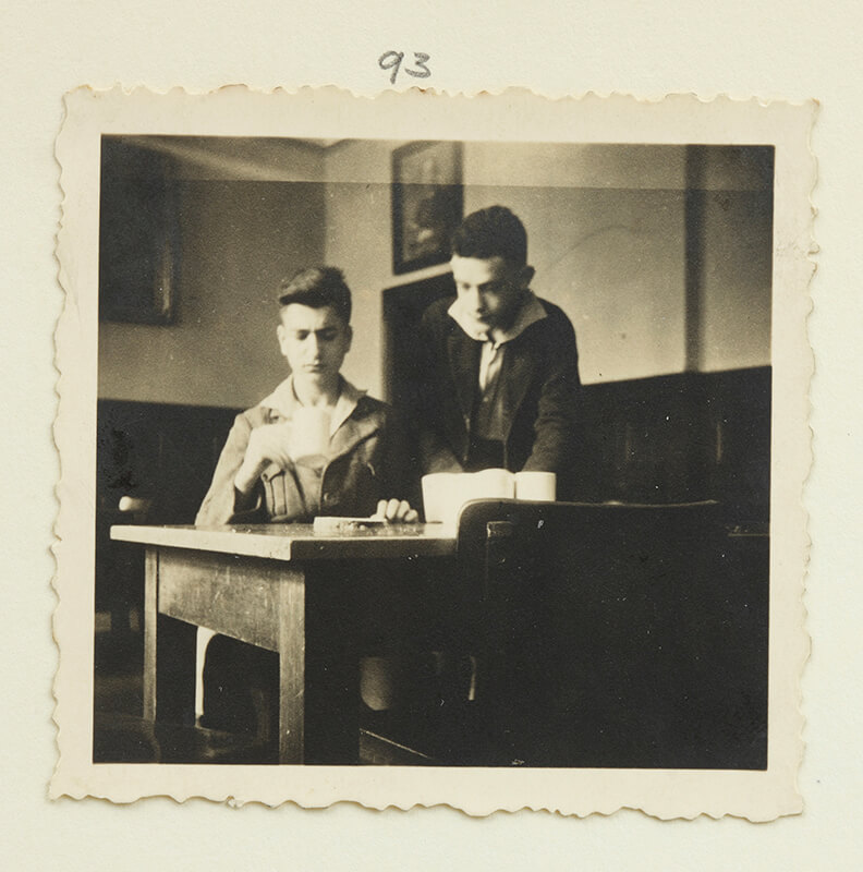 Two boys sitting at a table, one sitting with a cup, one standing behind him (black and white photo)