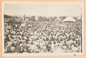 On the black and white picture photographed from diagonally above, a large crowd of people faces a house with a man standing on its roof and speaking to the crowd.