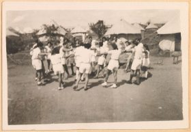 Black and white photography: Men and women dance in white shorts and white blouses in an inner circle and an outer circle, holding hands, holding out their left foot. The background shows white tents.