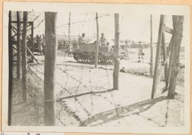 Black and white photography: Behind a wire fence are two tanks with soldiers. Around the tanks are internees.