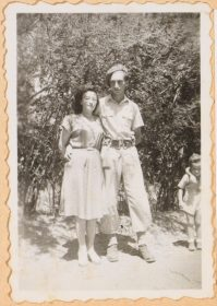 On the black and white picture Walter Frankenstein holds his wife Leonie in his arms. He wears a military uniform, Leonie a summer dress. They do not smile. Bushes grow in the background..