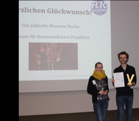 Under a screen on which the Traineeship Committee congratulates the winners of the prize, Franziska and David hold the certificate up to the camera.