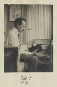 Black-and-white photo of Ludwig Scherk sitting in the living room, reading.