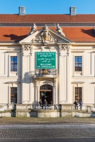 "The colour photo shows the façade of the Jewish Museum Berlin with a traffic sign with the inscription ""Welcome to Jerusalem"" in English, Arabic and Hebrew."