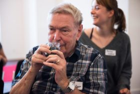 A man sniffs at a glass.