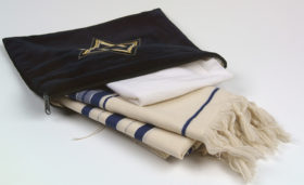 An ivory-coloured, blue striped tallit is half pulled out of its blackish cover, on the cover an embroidered star of David is visible.