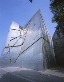 View of the titanium-zinc facade of the Libeskind building, which is broken up by slanting lines.