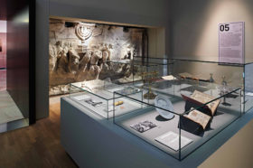A look into an exhibition room. On the rear wall, a plaster cast of the Arch of Titus can be seen. In the foreground stand a glass case with a menorah, Torah rimonim, and open books.