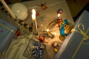 Menora mit einer angezündeten Kerze