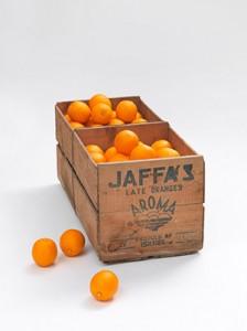 Eine mit Orangen gefüllte Kiste und drei daneben liegende Orangen
