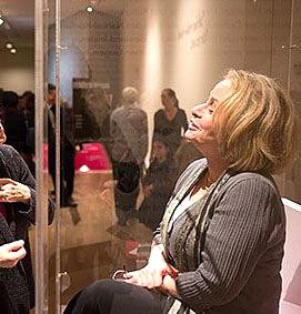 Eine Frau hinter Vitrinenglas, im Hintergrund Ausstellungsbesucher