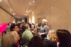 Eine Frau steht redend in der Vitrinenöffnung, davor eine Gruppe Zuhörende