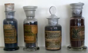 Vier Glasfläschchen mit Glasstöpseln und alten Etiketten