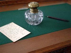 Gläsernes Tintenfass, Schreibfeder und Postkarte auf einem Schreibtisch