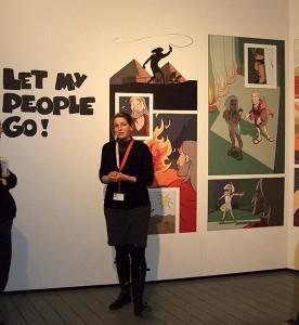 Eine junge Frau vor einem Comic an der Wand mit der Aufschrift »Let my people go!«