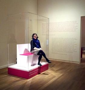 Eine Frau sitzt auf einer Bank in einem vorne offenen Glaskasten