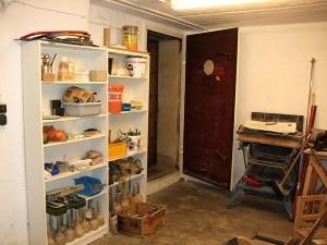 Regale mit Werkzeugen, Farben und weiteren Gegenständen neben einer geöffneten Tür