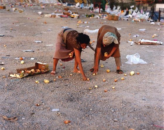 Künstlerisch inszeniertes Photo: zwei weibliche Figuren sammeln übriggebliebene Zwiebeln