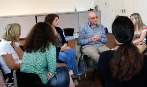 Ein älterer Herr und einige junge Frauen in einem Stuhlkreis